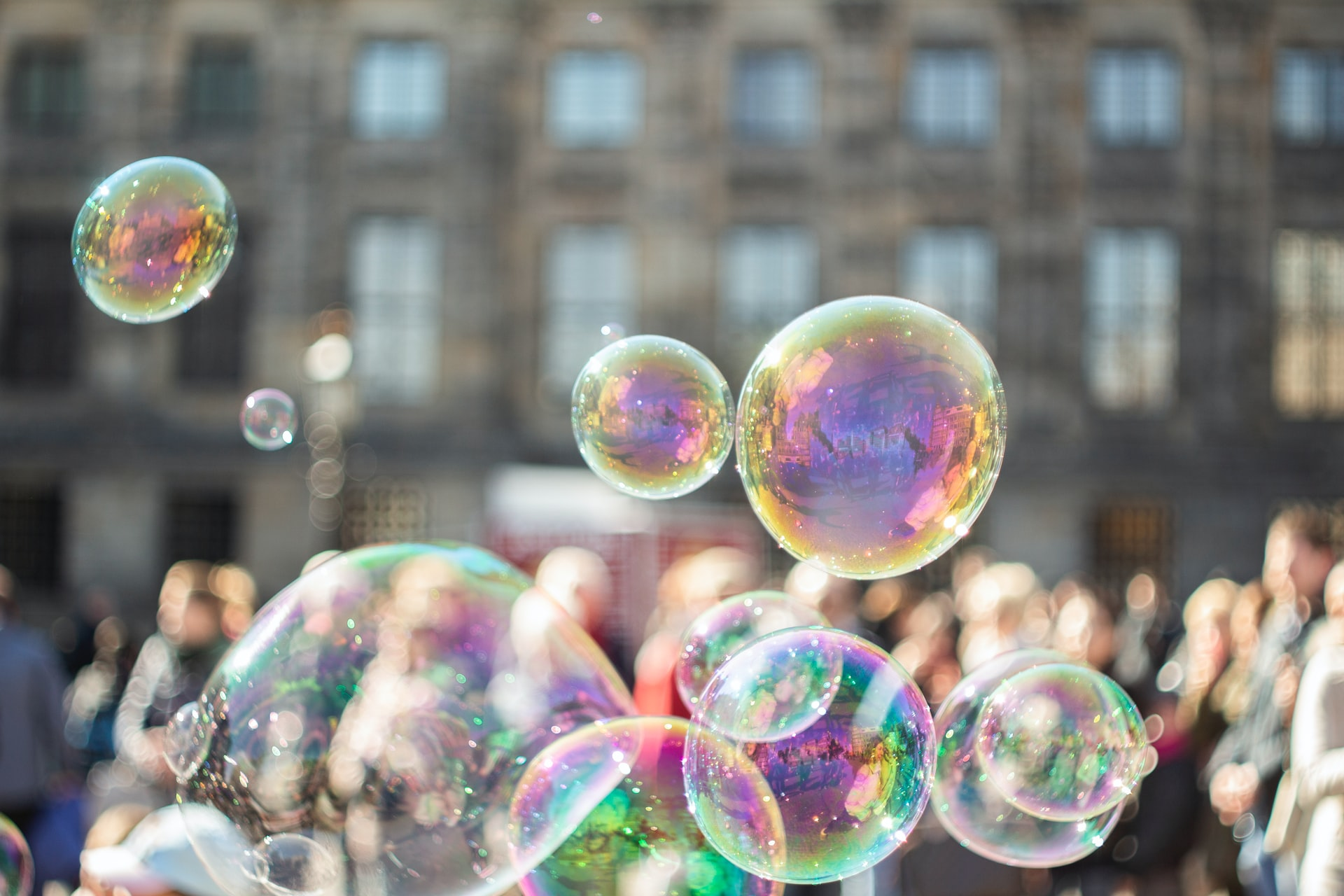 A photograph of bubbles in the foreground, with blurry people and a building in the background.