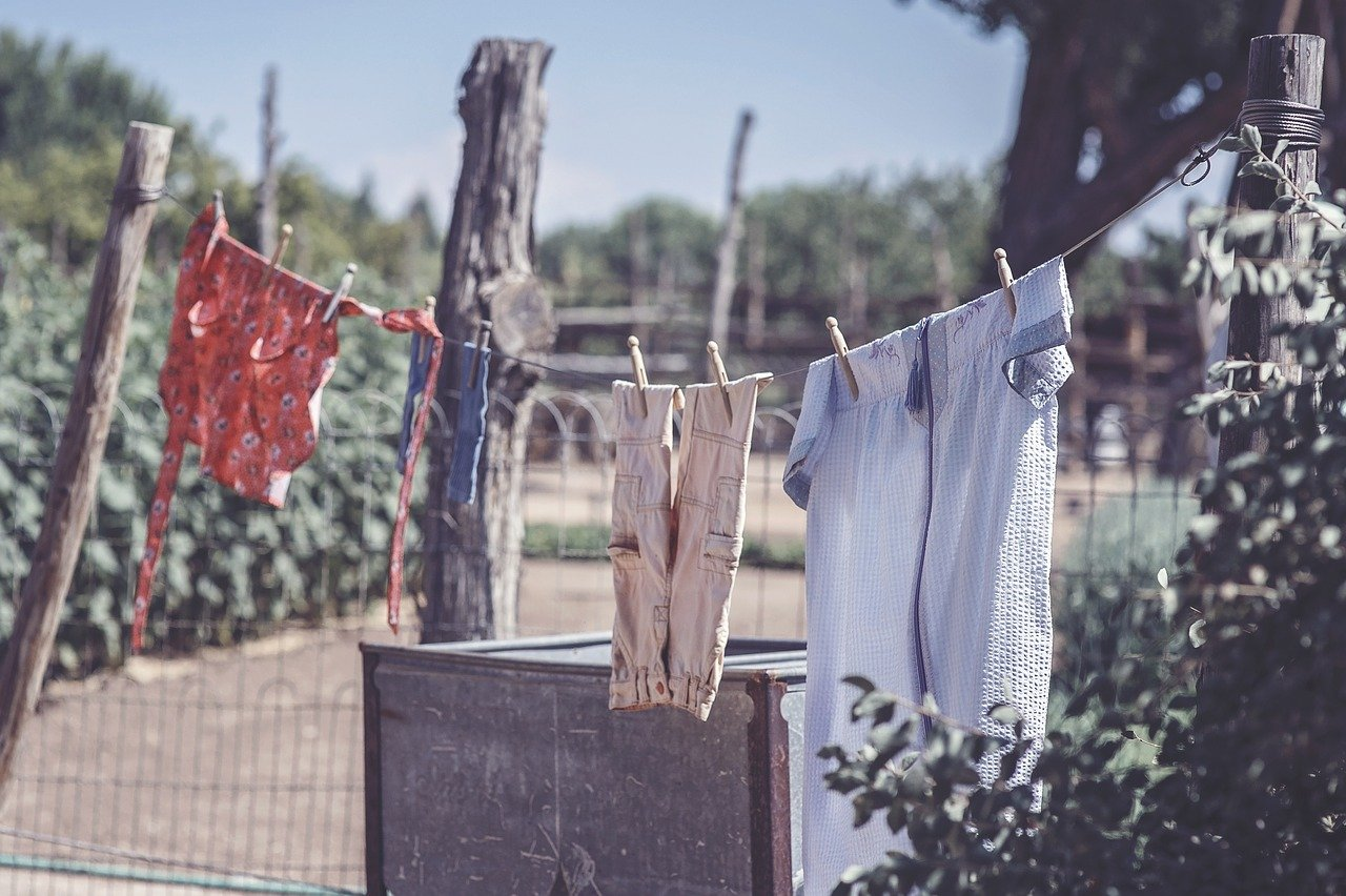 Photo of a clothesline with four articles of clothing, including children's cloths.